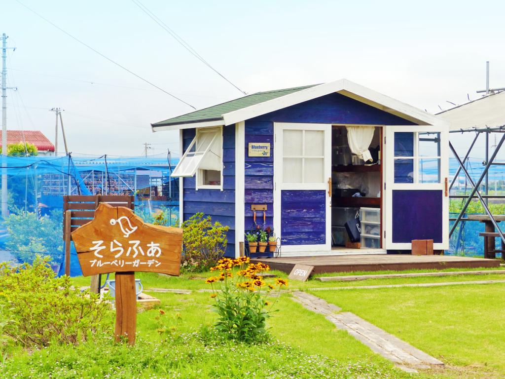そらふぁブルーベリーガーデンの看板と、園内の小屋の写真