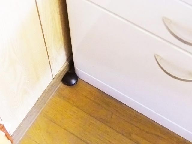 ゴキブリ駆除剤を家具の隙間付近に置く様子