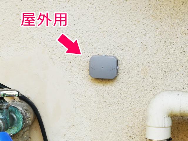 屋外用のゴキブリ駆除剤を建物の外壁に設置する様子