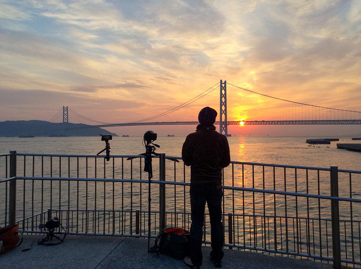 海辺で明石海峡大橋を見つめる筆者の後ろ姿