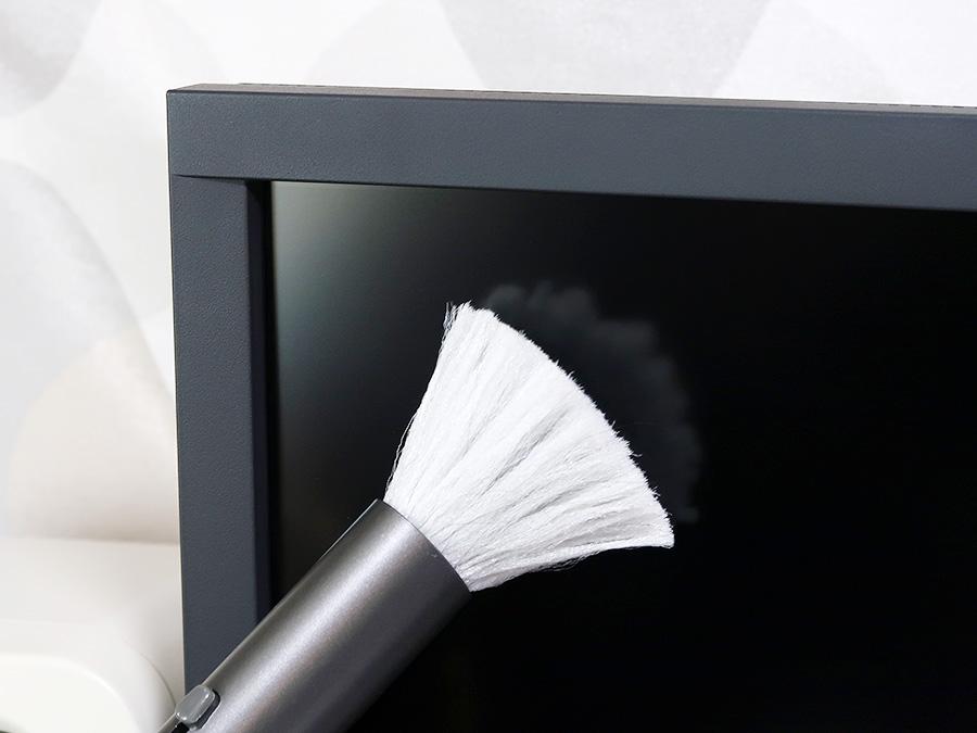 画面に付いたホコリを除電ブラシで取り除く様子